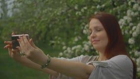 A mulher do estilo de vida toma um selfie no telefone em um jardim de floresc?ncia video estoque