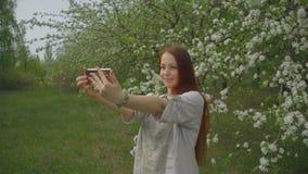 A mulher do estilo de vida toma um selfie no telefone em um jardim de floresc?ncia vídeos de arquivo