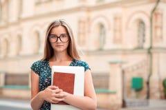 Mulher do estudante que guarda o port?til do PC dos livros que olha seguro fotografia de stock