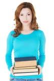 Mulher do estudante que guardara livros pesados Fotografia de Stock Royalty Free