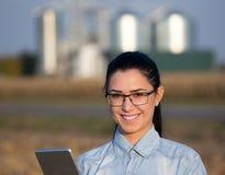 Mulher do fazendeiro com tabuleta e silos Imagem de Stock