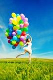 Mulher do feliz aniversario contra o céu com os vagabundos arco-íris-coloridos do ar Fotografia de Stock