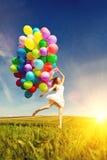 Mulher do feliz aniversario contra o céu com os vagabundos arco-íris-coloridos do ar Imagens de Stock