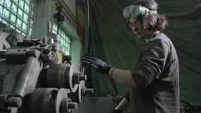 Mulher do ferreiro que põe uma barra de ferro em uma máquina de dobra do metal em sua oficina - video estoque