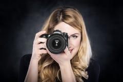 Mulher do fotógrafo que guarda a câmera fotografia de stock royalty free