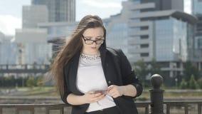 Mulher do gerente que usa o smartphoneno corrimão filme