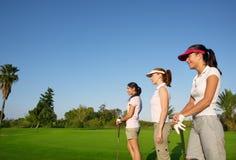 Mulher do golfe três em um curso da grama verde da fileira Fotos de Stock
