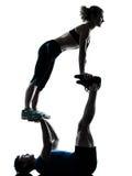 Mulher do homem que exercita a silhueta acrobática da aptidão do exercício fotografia de stock