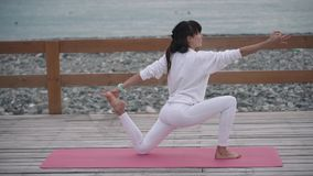 A mulher do instrutor da ioga está fazendo exercícios no seacoast filme