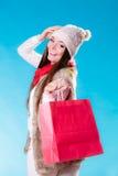 Mulher do inverno com o saco de compras de papel vermelho Fotografia de Stock