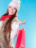 Mulher do inverno com o saco de compras de papel vermelho Fotografia de Stock Royalty Free