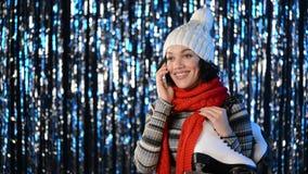 Mulher do inverno com os patins sobre o ombro que falam no telefone celular vídeos de arquivo
