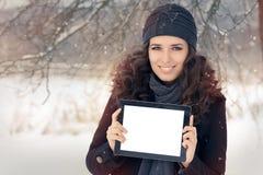 Mulher do inverno com tabuleta fora na neve Fotografia de Stock Royalty Free