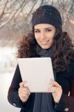Mulher do inverno com tabuleta fora na neve Foto de Stock Royalty Free