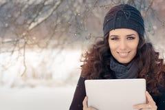 Mulher do inverno com tabuleta fora na neve Foto de Stock