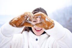 Mulher do inverno Conceito do amor e da caridade A mulher feliz mostra o coração Mãos da mulher no símbolo do coração das luvas d imagens de stock royalty free