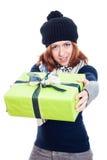 Mulher do inverno que dá o presente Fotografia de Stock