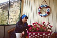 A mulher do jardim do cabelo escuro é semear flores Fotografia de Stock Royalty Free