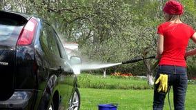 Mulher do jardineiro que lava seu carro com o jato de água forte no ar livre filme