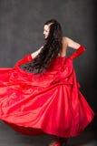 Mulher do Latino com cabelo longo na dança de ondulação vermelha do vestido na ação com tela do voo Fotografia de Stock