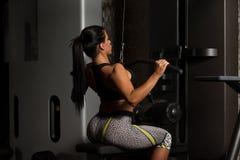 Mulher do Latino que faz o exercício para a parte traseira na máquina fotografia de stock