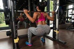 Mulher do Latino que faz o exercício pesado para a parte traseira foto de stock royalty free