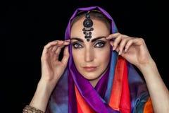 Mulher do leste no burqa com joias em um fundo preto fotografia de stock