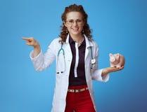 Mulher do médico com mealheiro que aponta em algo imagem de stock