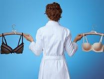 Mulher do médico que mostra o sutiã confortável e o sutiã 'sexy' no azul foto de stock