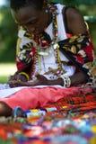 Mulher do Masai que seleciona grânulos imagens de stock