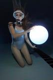Mulher do mergulhador com a esfera subaquática imagem de stock