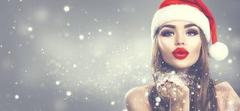 Mulher do modelo da beleza na neve de sopro do chapéu de Santa em sua mão Menina da forma do inverno do Natal no fundo borrado fe fotografia de stock royalty free