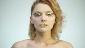 A mulher do modelo de alta-costura em dourado compõe o levantamento no estúdio Retrato da menina 'sexy' bonita, pele de incandesc filme