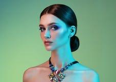 Mulher do modelo de alta-costura nas luzes brilhantes coloridas que levantam no estúdio foto de stock
