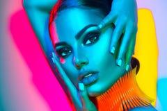 Mulher do modelo de forma em luzes brilhantes coloridas com composição na moda e tratamento de mãos Fotos de Stock
