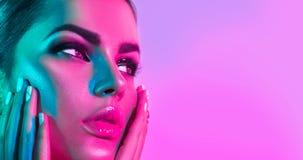 Mulher do modelo de forma em luzes brilhantes coloridas com composição na moda e tratamento de mãos Fotos de Stock Royalty Free