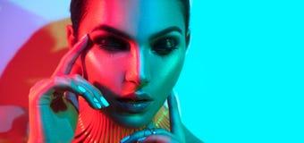 Mulher do modelo de forma em luzes brilhantes coloridas com levantamento na moda da composição e do tratamento de mãos Fotos de Stock