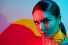 Mulher do modelo de forma em luzes brilhantes coloridas com a mulher modelo na moda da composição e do manicureFashion no levanta Foto de Stock Royalty Free