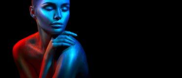 Mulher do modelo de forma em sparkles brilhantes coloridos e nas luzes de néon que levantam no estúdio, retrato da menina 'sexy'  fotografia de stock royalty free