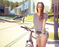 Mulher do moderno da forma com a bicicleta na cidade Fotografia de Stock Royalty Free