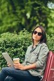 Mulher do moderno no óculos de sol com um café e um tablet pc Foto de Stock Royalty Free