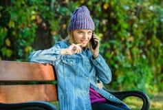 Mulher do moderno para falar no telefone A menina tem a conversação de telefone celular no parque relaxe no banco em srpring Conc fotografia de stock royalty free