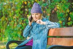 Mulher do moderno para falar no telefone A menina tem a conversa??o de telefone celular no parque relaxe no banco em srpring Conc imagens de stock