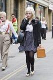 a mulher do moderno vestiu-se no estilo fresco do londrino que anda na pista do tijolo, uma rua popular entre povos na moda novos Fotografia de Stock Royalty Free