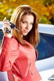 Mulher do motorista que mostra chaves novas do carro e carro. Imagem de Stock