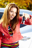 Mulher do motorista que mostra chaves novas do carro e carro. Imagens de Stock Royalty Free
