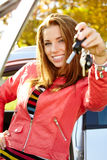 Mulher do motorista que mostra chaves novas do carro e carro. Imagens de Stock
