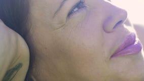 A mulher do movimento lento olha acima de sonhar a sesta, sorriso sustentando da cabeça da mão agradável video estoque