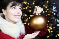 A mulher do Natal com bola, sorrindo e olha acima Fotos de Stock