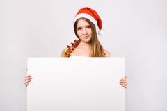 Mulher do Natal no chapéu de Santa com quadro de avisos em branco Foto de Stock